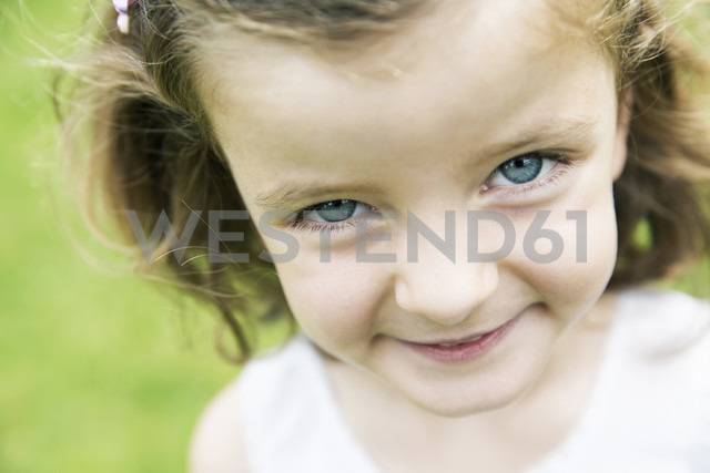 Smiling little girl with blue eyes watching at camera - JATF000413