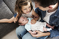 Young father with male newborn and little daughter sitting on sofa at home - JATF000426