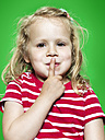 Portrait of little girl with forefinger on her lips, studio shot - STKF000373