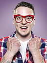 Portrait of happy young man with red glasses, studio shot - STKF000400
