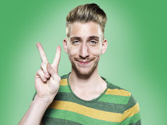 Portrait of young man showing victory sign, studio shot - STKF000409