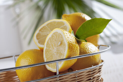 Sliced and whole lemons in basket, studio shot - CSF020174