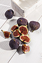 Sliced and whole figs on white wooden table, studio shot - CSF020196