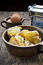 Uncooked tagliatelle and eggs on wooden table - LVF000245