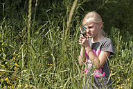 Girl looking through magnifying glass in garden - KJF000268