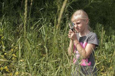 Girl looking through magnifying glass in garden - KJF000268
