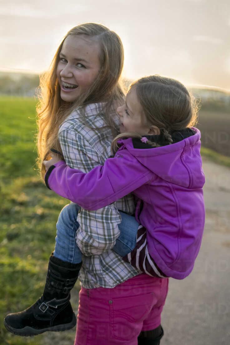Teenage girl carrying girl piggyback - SAR000118 - Sandra Rösch/Westend61