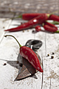 Red chili peppers (Capsicum) and an old knife on white wooden table, studio shot - CSF020282