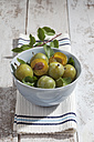 Sliced and whole greengages (Prunus domestica subsp. italica var. claudiana) in a bowl on white wooden table, studio shot - CSF020244