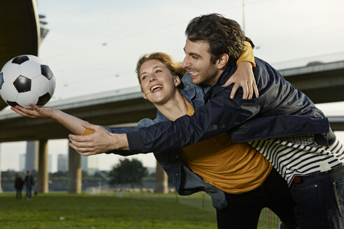 Germany, Dusseldorf, Young couple playing football - STKF000455