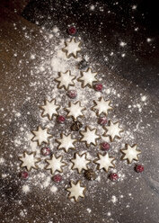 Christmas tree formed of star-shaped cinnamon cookies, red berries and fir cones on wooden table - SARF000133