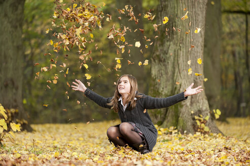 Crouching girl throwing autumn leaves in a forest - PA000036