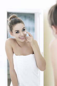 Portrait of smiling teenage girl looking at her mirror image - GDF000252