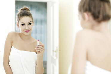 Portrait of teenage girl with lipstick looking at her mirror image - GDF000257