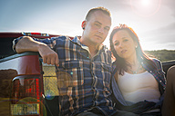 USA, Texas, Young couple sitting on truck bed - ABAF001033