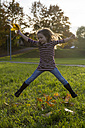 Jumping little girl with autumn leaves in her hands - SAR000125