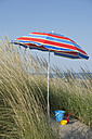 Italy, Adriatic, bucket and shovel under sunshade on sand dune with grass - CRF002503