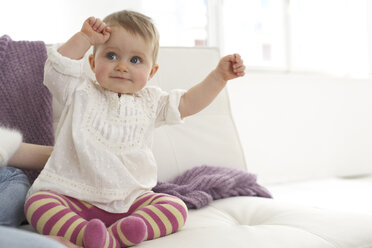 Smiling baby girl with outstrechted arms sitting on sofa - FSF000023