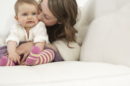 Mother kissing her smiling baby girl - FSF000026