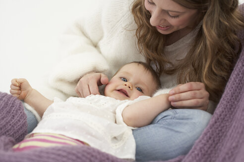 Smiling baby girl lying on her mothers legs - FSF000027