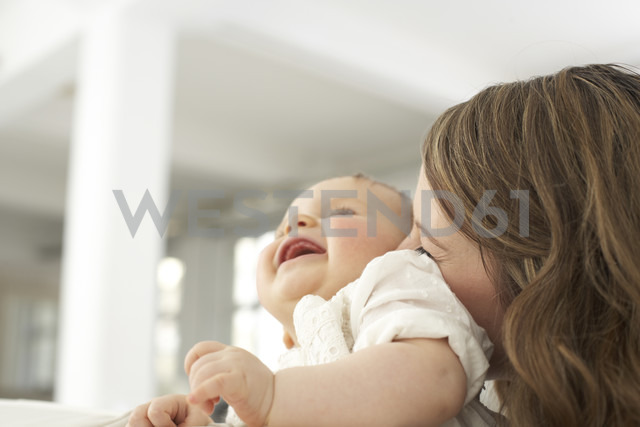 Mother kissing her laughing baby girl - FSF000029