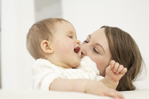 Mother kissing her smiling baby girl - FSF000030