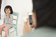 Asian woman photographing her little daughter with smartphone - FSF000086