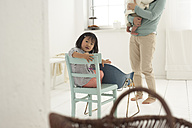 Little Asian girl sitting on a chair, mother and sister in the background - FSF000091