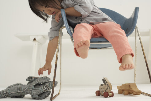 Little Asian girl sitting on a chair gribbing her soft toy - FSF000071