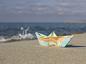 Spain, Formentera, little paper boat folded of a map lying on sandy beach at shore - CM000008