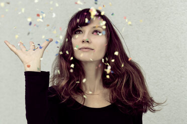 Young woman looking at confetti in the air - NGF000046