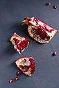 Pits and three pieces of pomegranate [Punica granatum] on blue wood, studio shot - MYF000057