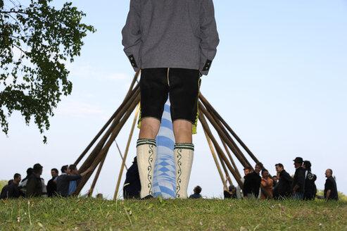 Germany, Bavaria, Man watching people posting maypole - LH000299