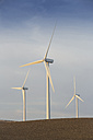 Spain, Andalusia, Cadiz, three wind turbines standing on a field - KBF000006