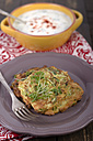 Bowl of yoghurt dip with garlic and mint and a plate with zucchini fritters, studio shot - ODF000636