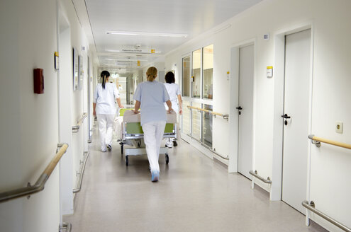 Germany, Freiburg, Nurses moving hospital bed - DHL000135