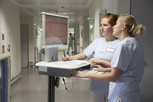 Germany, Freiburg, Nurses with mobile computer deskte, checking patient data - DHL000147