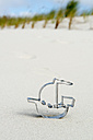 Germany, Amrum, Boat shaped cookie cutter on sand dune - AWDF000733