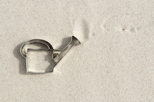 Watering can shaped cookie cutter on sand - AWDF000704