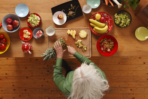 Germany, Dusseldorf, Senior woman preparing raw food - UKF000235