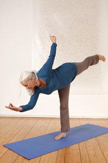 Germany, Dusseldorf, Senior woman practicing yoga - UKF000239