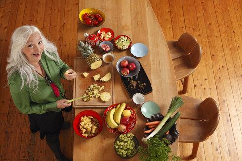 Germany, Dusseldorf, Senior woman preparing raw food - UKF000252