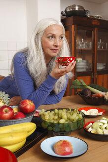 Germany, Dusseldorf, Senior woman with raw food drinking tea - UKF000233