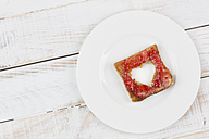Toast with red jam and heart-shaped hole on plate, studio shot - DRF000267