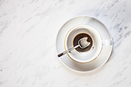 Cup of coffee with vestiges of coffee on white marble panel - SBDF000344