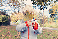 Germany, Bonn, Baby boy covering face with  autumnal leaf i - MFF000615