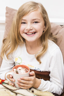 Smiling little girl covered with chocolate holding cup of cacao, studio shot - STB000158