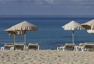 Spain, Formentera, Es Arenals, sunshades and beach chairs - CM000018