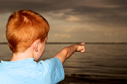 Germany, Schleswig-Holstein, Flensburg Fiord, Boy pointing at sea - JEDF000036