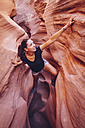 USA, Utah, Escalante, Peek-A-Boo and Spooky Slot Canyons, young woman climbing in gorge - MBEF000822